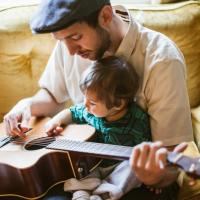 Dad and child practice guitar