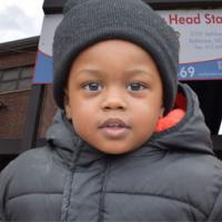Smiling little boy bundled up in from of Early Head Start center
