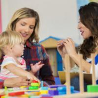 Mother and daughter work with preschool teacher. They are sitting at a table in the classroom working with educational toys.