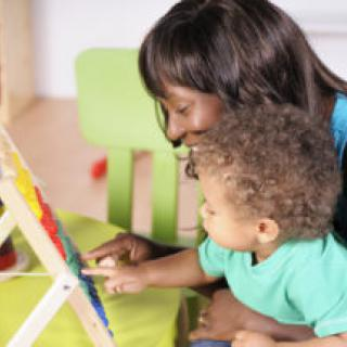 Close-up view of biracial baby/toddler and African-American woman using abacus to learn through play.