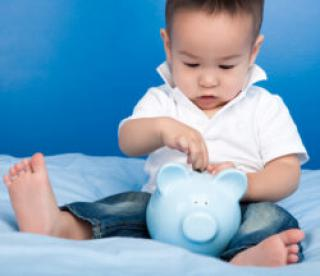 Boy putting money in blue piggy bank