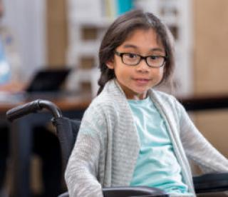 Pretty elementary age girl in wheelchair waits in doctor's office waiting room.